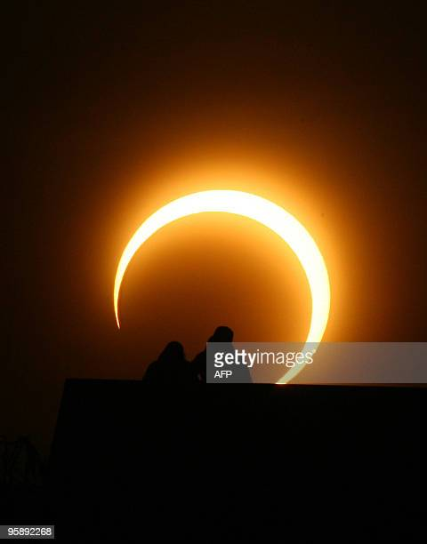 A Chinese couple watches the solar eclipse over Zhengzhou central China's Henan province on January 15 2010 A solar eclipse that reduced the sun to a...