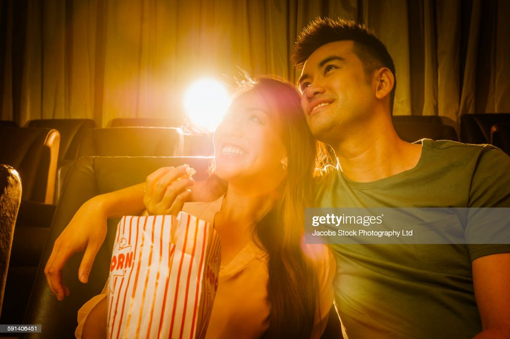 Chinese couple watching film in movie theater : Stock Photo