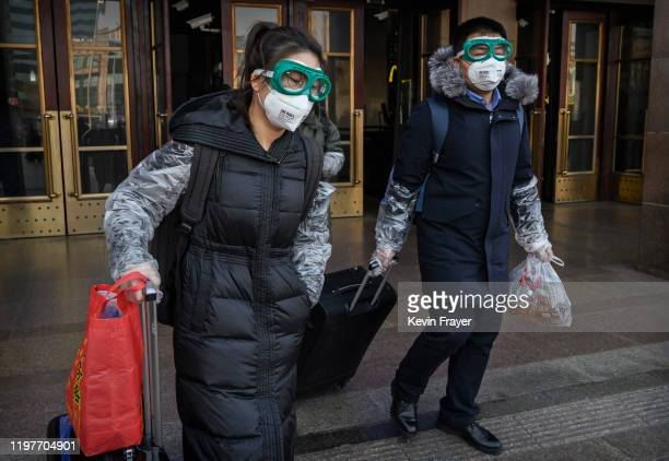 Chinese couple wear protective masks and goggles after getting off a train as they and others return after the Spring Festival holiday on January 31...