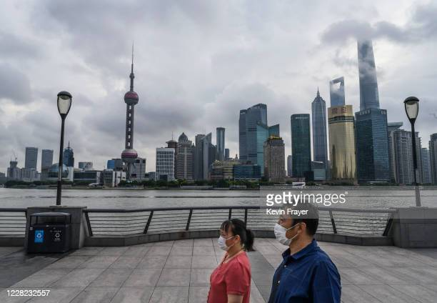 Chinese couple wear protective masks as they walk along the Huangpu River as the skyline of the city is is seen, including the Oriental Pearl TV...
