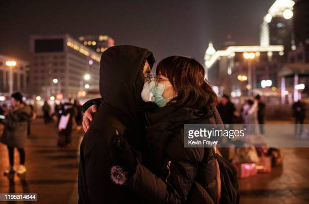 Chinese couple wearing their protective masks kiss before saying goodbye to catch a train at Beijing Station before the annual Spring Festival on...