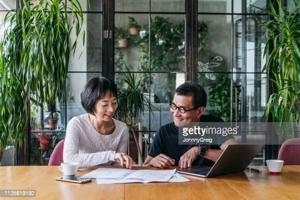 casal chinês com laptop discutindo a papelada e sorrindo - etnia oriental - fotografias e filmes do acervo
