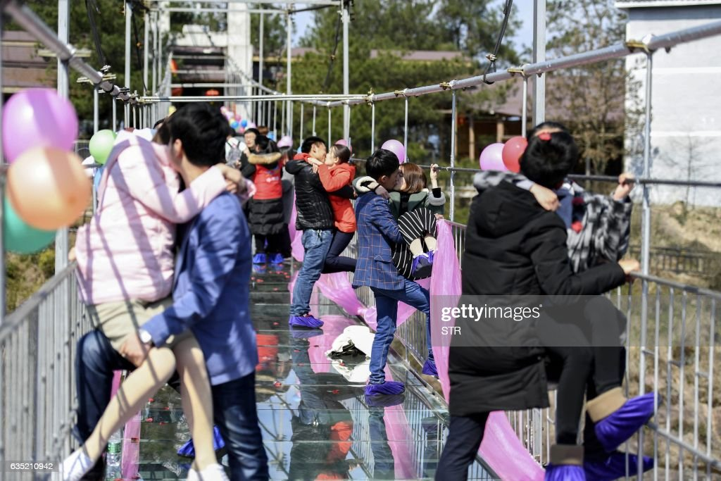 Chinese couples kiss as they stand on a glass bridge during a kissing contest on Valentine's Day in Pingjiang, central China's Hunan province on February 14, 2017. / AFP / STR / China OUT