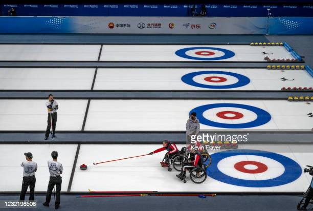 Chinese curler Shao Sheng Ping, center, throws a rock as teammate Yan Zhou assists and Chen Jian Xin, right, looks on during the wheelchair curling...