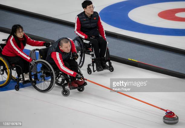 Chinese curler Shao Sheng Ping throws a rock as teammate Yan Zhou assists and Chen Jian Xin looks on during the wheelchair curling test event for the...