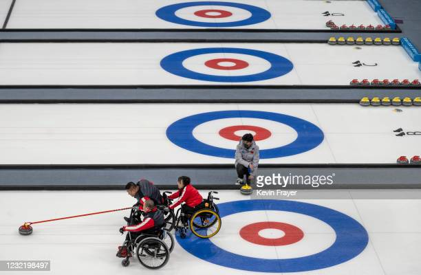 Chinese curler Wang Haitai throws a rock during the wheelchair curling test event for the Beijing 2022 Winter Paralympics at the Ice Cube on April 9,...