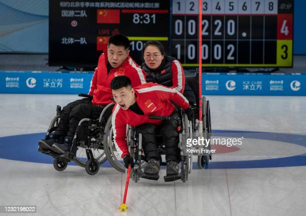 Chinese curler Zhang Ming Ling, front, shouts for the sweep as teammates Liu Wei and Wang Meng, right, look on after throwing a rock during the...