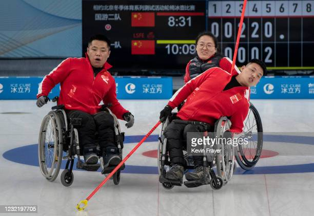 Chinese curler Zhang Ming Ling,front right, leans as he watches his shot with teammates Liu Wei, left, and Wang Meng after throwing a rock during the...