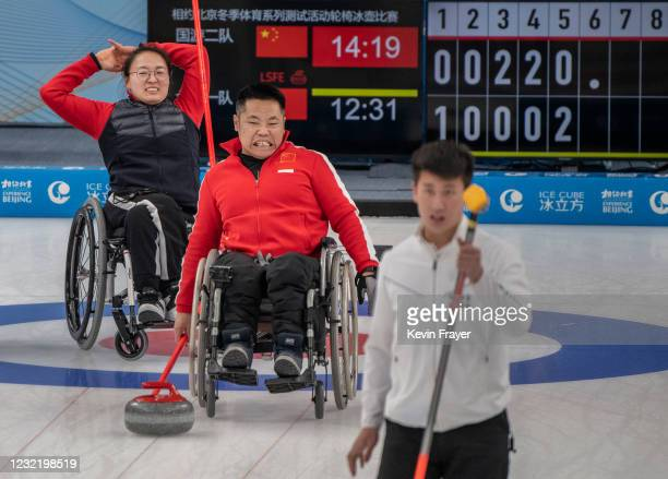 Chinese curlers Liu Wei, center, and Wang Meng react to an opponents throw during the wheelchair curling test event for the Beijing 2022 Winter...