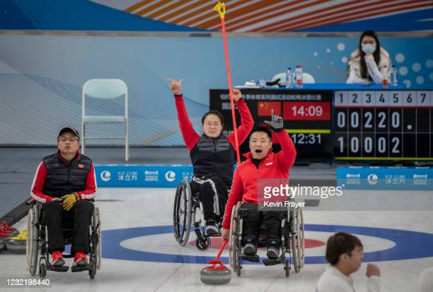 Chinese curlers Liu Wei, right, and Wang Meng react as teammate Liu Wei looks on during the wheelchair curling test event for the Beijing 2022 Winter...