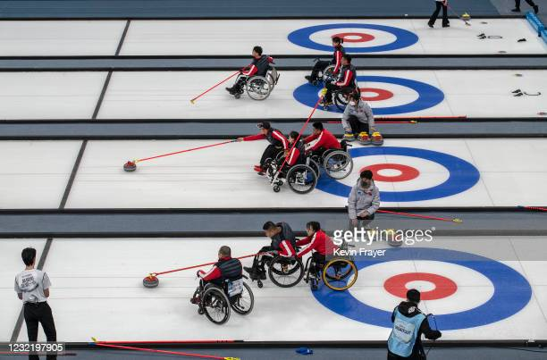 Chinese curlers throw rocks as teammates look on during the wheelchair curling test event for the Beijing 2022 Winter Paralympics at the Ice Cube on...