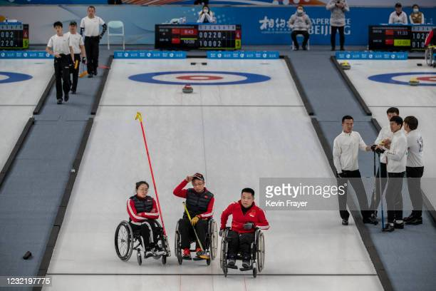 Chinese curlers, Wang Meng, Zhang Qiang, and Liu Wei discuss strategy during the wheelchair curling test event for the Beijing 2022 Winter...