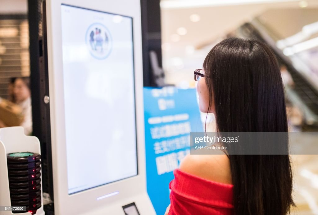 A Chinese customer experiences a facial recognition payment system, also known as the 'Smile to Pay' system, at a KFC fast food restaurant in Hangzhou in China's eastern Zhejiang province on September 1, 2017. The operator of KFC in China is rolling out a futuristic system of paying at a fast-food counter via facial recognition, as the country embraces the technology for everything from toilet paper to travel. / AFP PHOTO / STR / China OUT