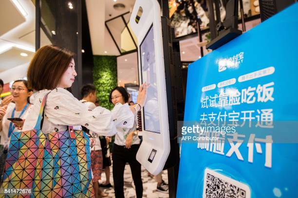 A Chinese customer experiences a facial recognition payment system also known as the 'Smile to Pay' system at a KFC fast food restaurant in Hangzhou...