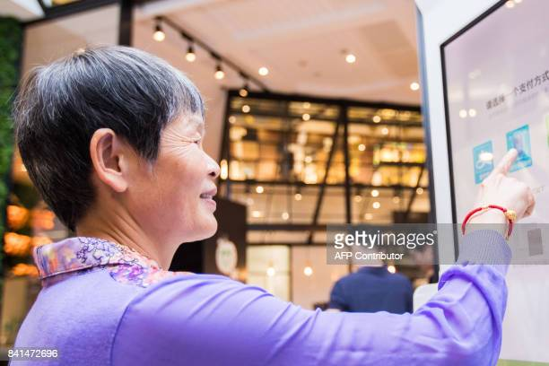 A Chinese customer experiences a facial recognition payment system also known as the Smile to Pay system at a KFC fast food restaurant in Hangzhou in...
