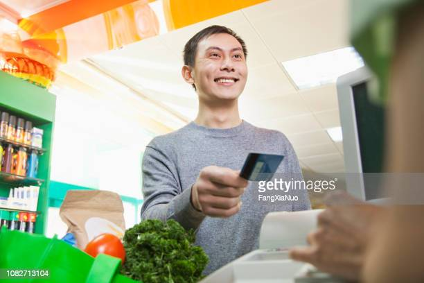 chinese customer handing cashier credit card in grocery store - gift card imagens e fotografias de stock