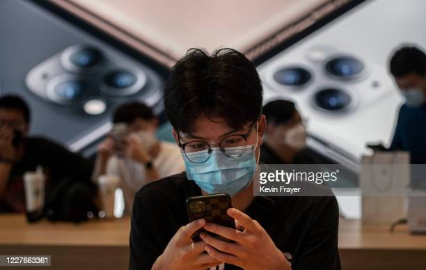 Chinese customer looks at a phone at the official opening of the new Apple Store in the Sanlitun shopping area on July 17 2020 in Beijing China The...