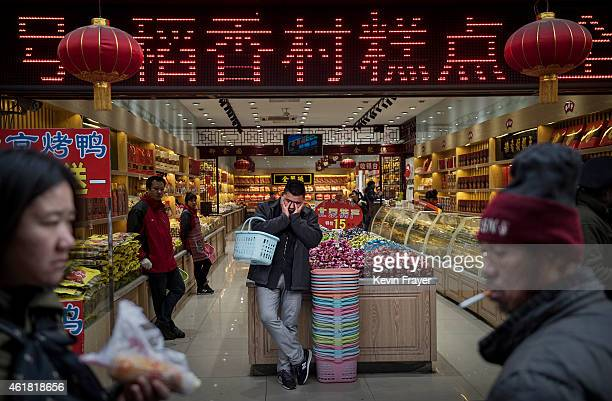 Chinese customer rests as he stands in a store in a shopping district on January 20 2015 in central Beijing China China's economic growth slowed to...