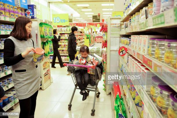 A Chinese customer selects milk powder at a supermarket in Qingdao east China's Shandong province on February 14 2017 Prices for goods at the factory...