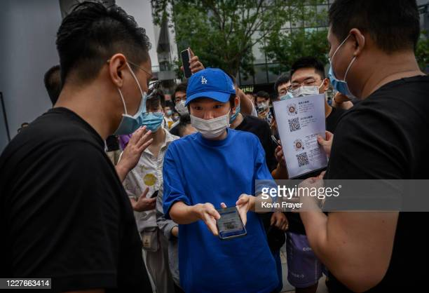 Chinese customer shows a health app on his phone as he passes security at the official opening of the new Apple Store in the Sanlitun shopping area...