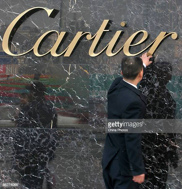 A Chinese customer touches the Cartier logo outside of luxury giant Cartier store on November 25 2005 in Guangzhou of Guangdong Province China...