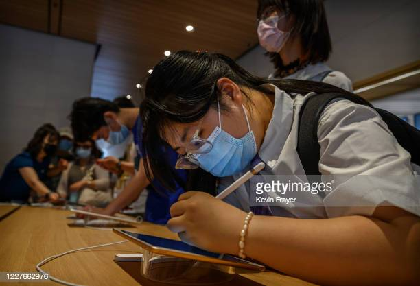 Chinese customer tries an ipad at the official opening of the new Apple Store in the Sanlitun shopping area on July 17 2020 in Beijing China The new...