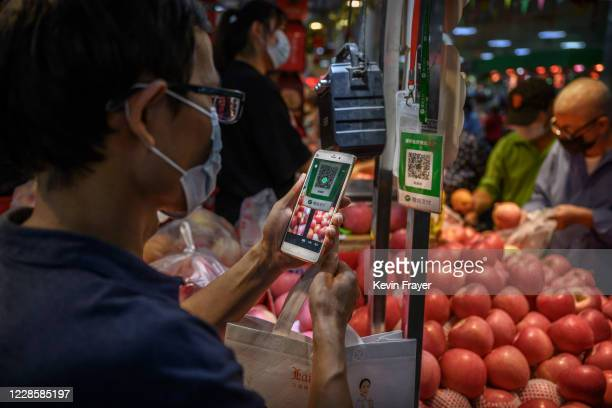 Chinese customer uses his mobile to pay via a QR code with the WeChat app at a local market on September 19, 2020 in Beijing, China. The Trump...