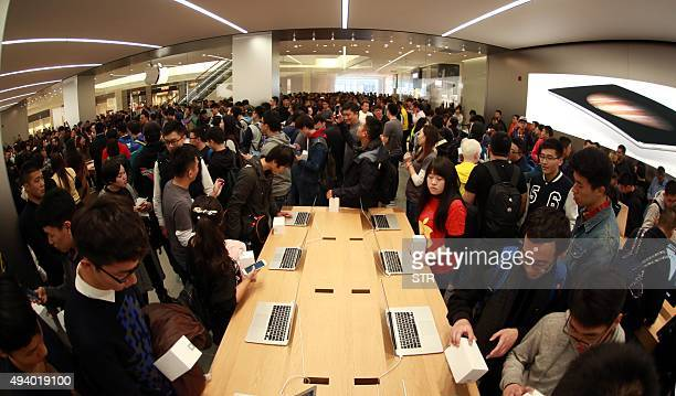 Chinese customers browse products at the opening of a new Apple store in Dalian China's Liaoning province on October 24 2015 US technology giant...
