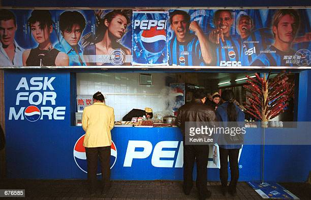 Chinese customers buy snacks January 12 2001 from a store decorated with ads for an American soft drink company in Beijing China The Chinese...