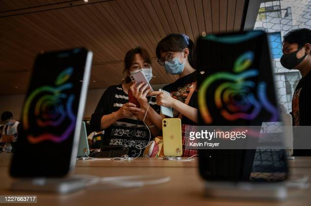 Chinese customers look at iphones at the official opening of the new Apple Store in the Sanlitun shopping area on July 17 2020 in Beijing China The...