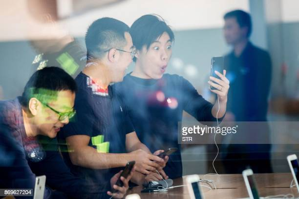 Chinese customers look at the new iPhone X at the Apple store in Hangzhou in China's eastern Zhejiang province on November 3 2017 Apple profits...