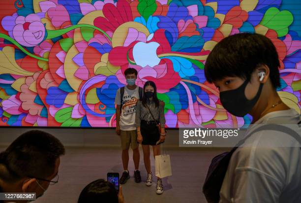 Chinese customers pose for a photo in front of a large screen at the opening of the new Apple Store in the Sanlitun shopping area on July 17 2020 in...