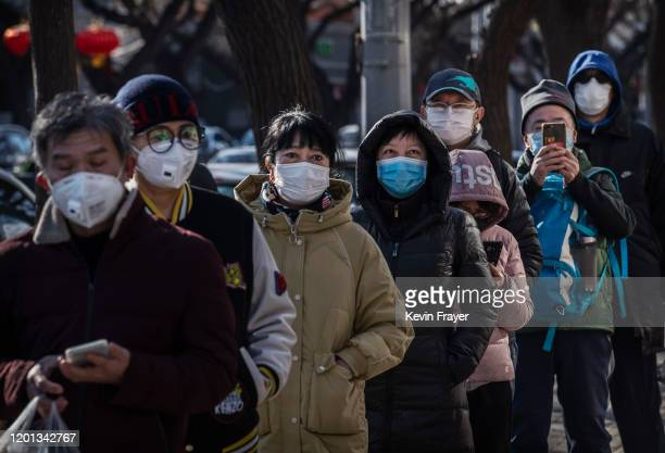 Chinese customers wear protective masks as they line up single file to buy dumplings at a popular local shop on February 16 2020 in Beijing China The...