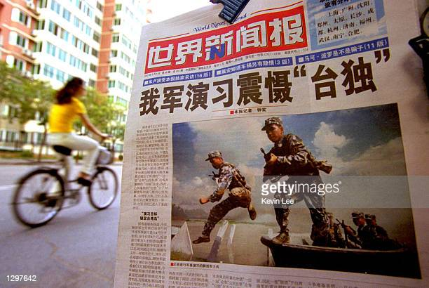 Chinese cyclist rides by a newspaper with a front page photo featuring the People's Liberation Army soldiers in military exercise with the headline...