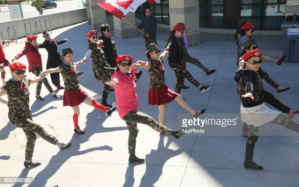 Chinese dancers dressed in military fatigues practice before a performance during Crime Prevention and Awareness Day in Mississauga Ontario Canada...