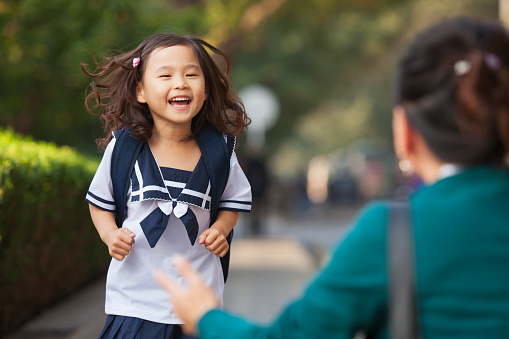Chinese daughter running to greet her mother 1082658994