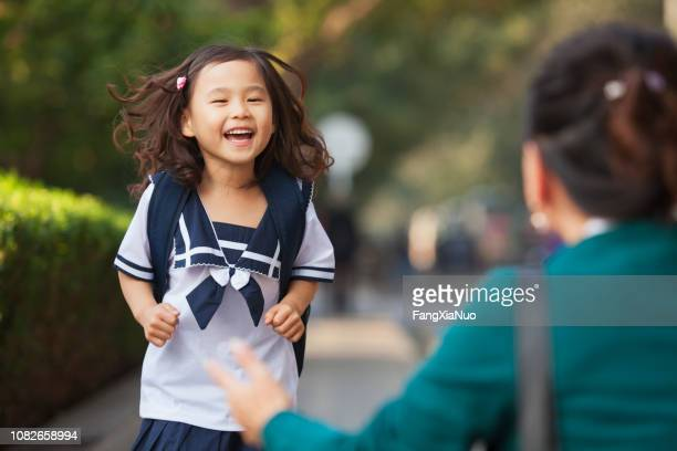 chinese daughter running to greet her mother - picking up stock pictures, royalty-free photos & images