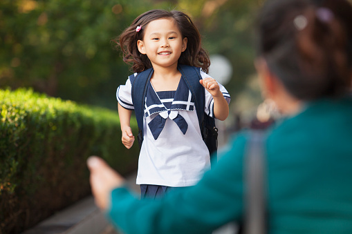 Chinese daughter running to greet her mother 1082659010