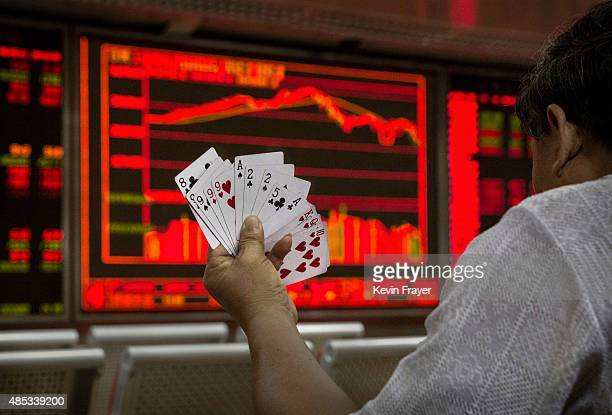 Chinese day trader plays cards wit5h others as he watches a stock ticker at a local brokerage house on August 27 2015 in Beijing China A dramatic...