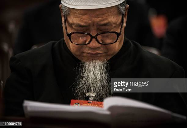 Chinese delegate of the Hue Muslim minority rests his eyes while reading during the third plenary session of the National People's Congress at The...