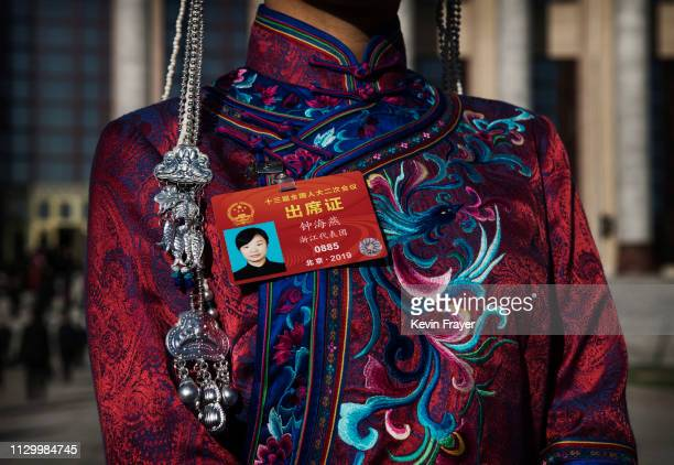Chinese delegate wears traditional clothing and her name tag as she arrives for the third plenary session of the National People's Congress at The...