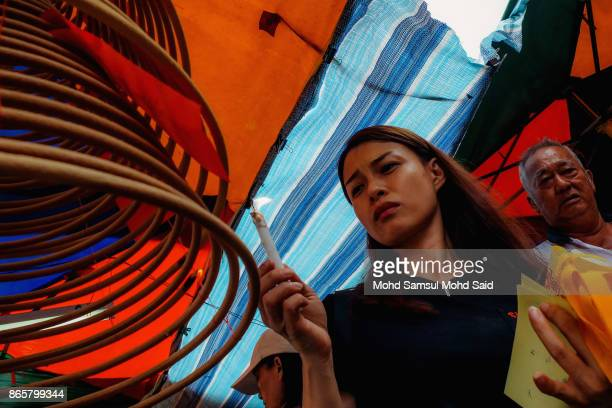 Chinese devotee lights a joss stick as she performs a prayer during The Nine Emperor Gods Festival inside the temple on October 24 2017 in Kuala...