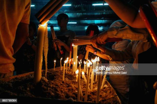 Chinese devotees lightup joss sticks as they perform prayer during The Nine Emperor Gods Festival inside the temple on October 24 2017 in Kuala...