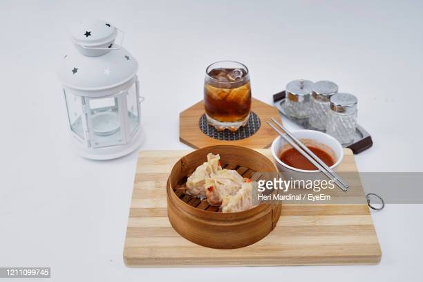 chinese dim sum in a bamboo steamer with white background - heri mardinal stock pictures, royalty-free photos & images