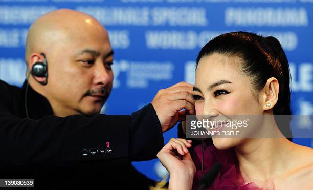 """Chinese director Wang Quan'an fixes the headphone of Chinese actress Zhang Yuqi during a press coneference to present the film """"White Deer Plain"""" at..."""