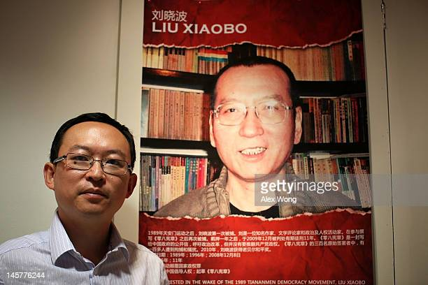 Chinese dissident and author Yu Jie poses for a picture in front of a poster of the 2010 Nobel Peace Prize winner Liu Xiaobo after an interview with...