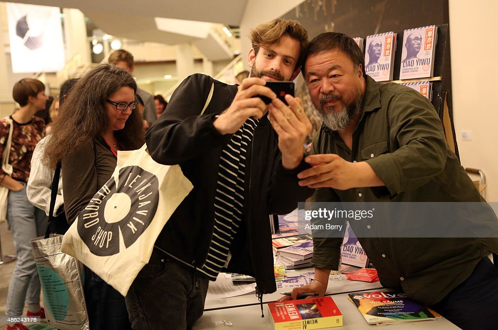 Chinese dissident artist Ai Weiwei poses for a selfie with a fan as he gives autographs after a panel discussion at the Berlin International Literature Festival on September 2, 2015 in Berlin, Germany. Ai and poet Liao Yiwu participated in a conversation about literature, contemporary art, and their relationships with Chinese authorities. Liao had been imprisoned for four years in 1989, and in 2011, Ai was detained and beaten by security officials and then imprisoned for 81 days, only to reclaim his passport this past July, after which he went to Germany to meet his his partner Wang Fen and their son Ai Lao.
