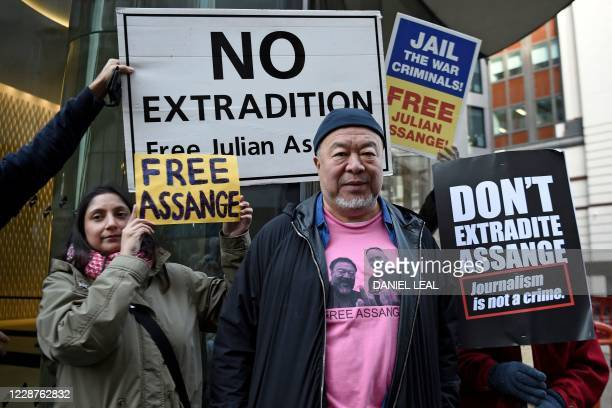 Chinese dissident artist Ai Weiwei poses with protesters outside the Old Bailey court in central London on September 28 where the extradition hearing...