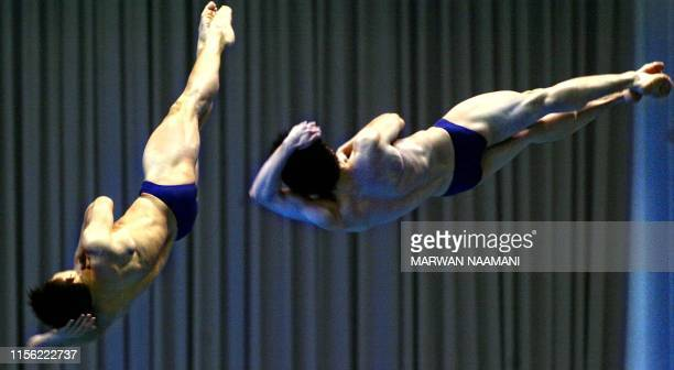 Chinese divers Wang Kenan and Peng Bo flip in the air in the final of the men's 3m sychronized diving event 09 October 2002 at Sajik pool in Busan...