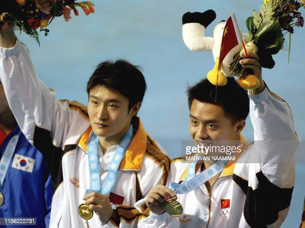 Chinese divers Wang Kenan and Peng Bo show off their medals after the final of the men's 3m sychronized diving event 09 October 2002 at Sajik pool in...
